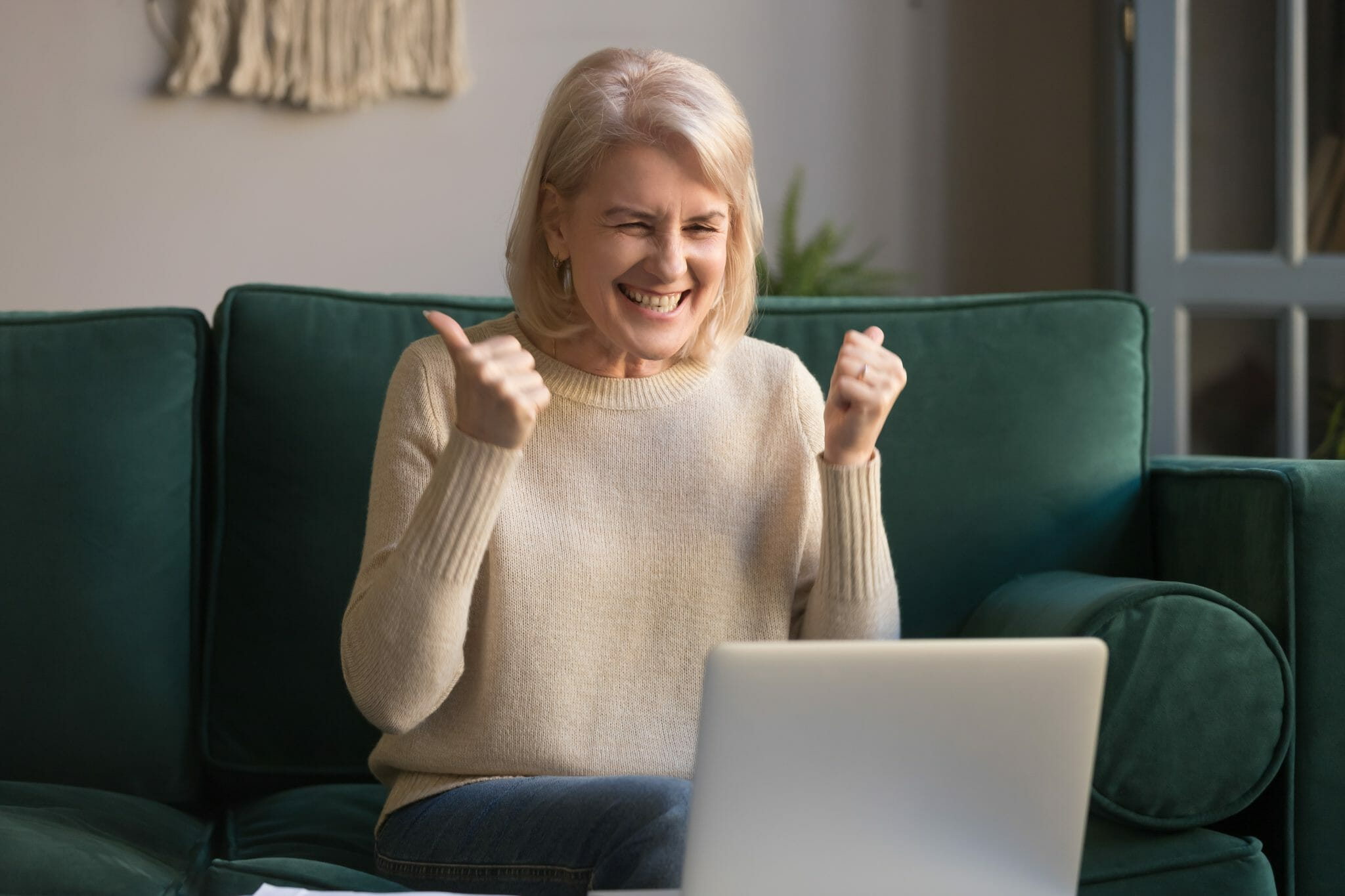 Woman giving herself a thumbs up while looking at a laptop