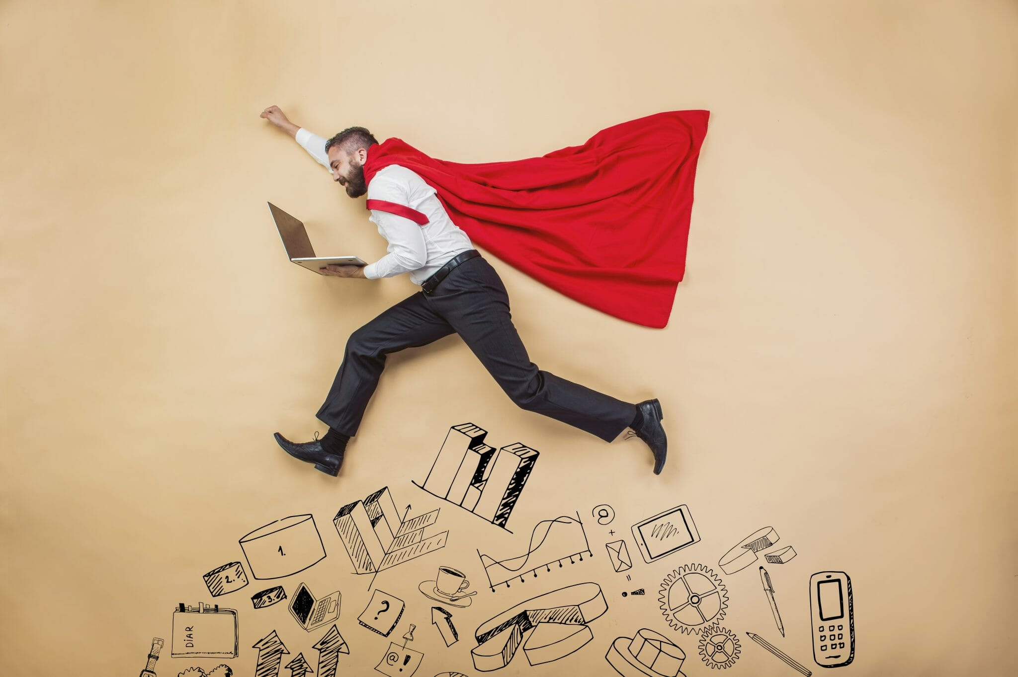 Man in cape holding computer leaping over various devleopment related graphics drawn on a wall